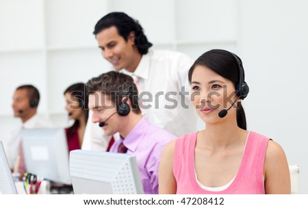 Confident manager checking his employee's work in a call center - stock photo