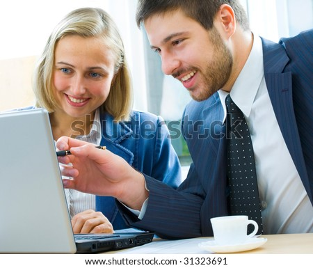 Confident manager discussing with colleague a project pointing at laptop - stock photo