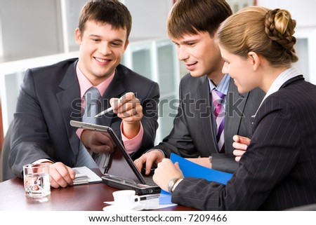 Confident manager is explaining the correct way of analysis to his colleagues in  the office pointing at the monitor - stock photo