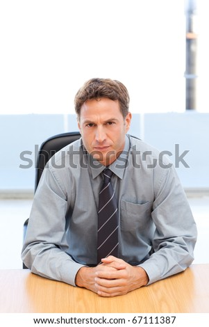Confident manager posing alone at a table in an office - stock photo