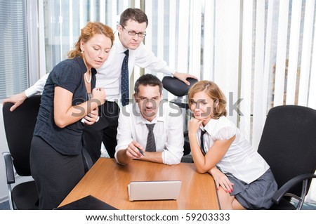 Confident manager speaking with his office workers in board room Hi Res. Business people looking at the information represented on laptop computer attentively indoors. - stock photo