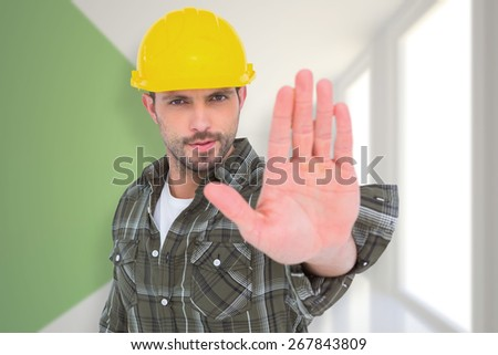 Confident manual worker gesturing stop sign against modern white and green room with window - stock photo
