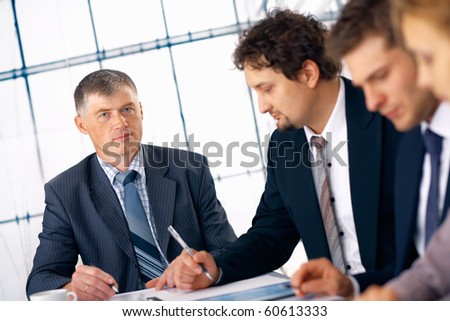 Confident mature business man with his staff working at the office. - stock photo