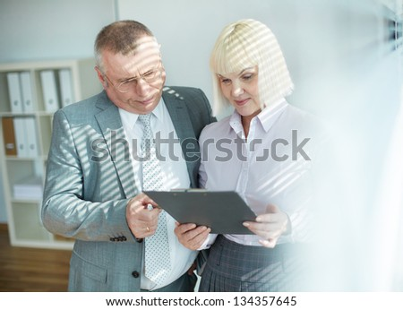 Confident mature businessman explaining something to his colleague while discussing document at meeting - stock photo