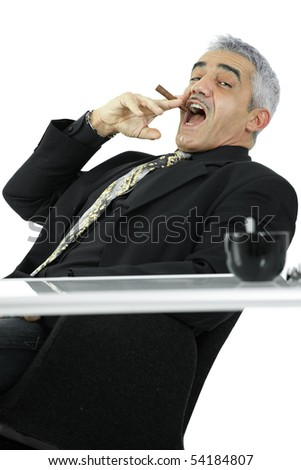 Confident mature businessman sitting at desk leaning back, smoking cigar. Isolated on white.