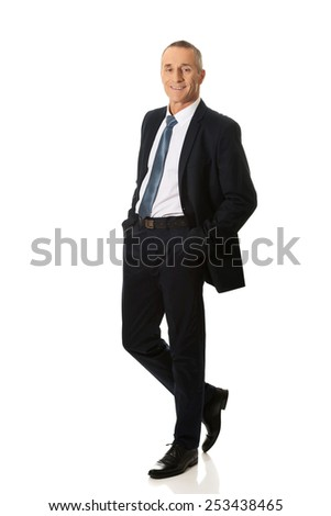 Confident mature businessman with hands in pockets. - stock photo