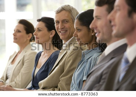Confident mature businessman with team seated in line with him - stock photo