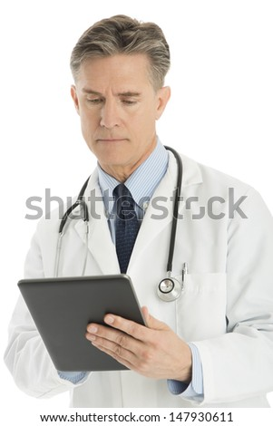 Confident mature male doctor using digital tablet isolated over white background - stock photo