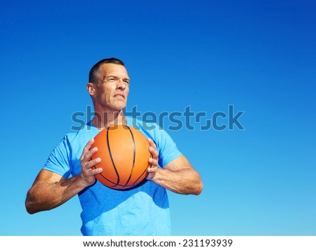 Confident mature man holding basketball against clear blue sky - stock photo