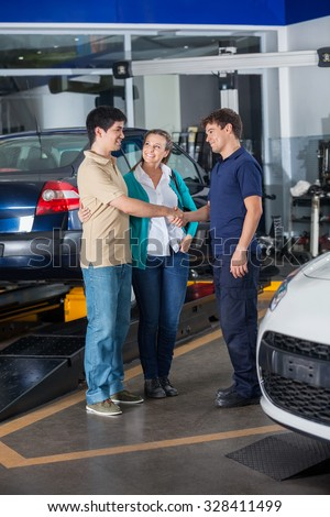 Confident mechanic shaking hand with couple at auto repair shop - stock photo