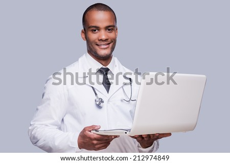 Confident medical doctor. Confident African doctor holding laptop and smiling while standing against grey background - stock photo