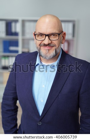 Confident middle-aged bearded businessman with a friendly smile standing with is hands in his pockets facing the camera, upper body portrait - stock photo