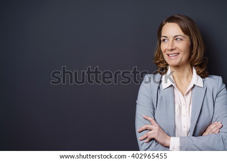 Confident middle-aged businesswoman standing with folded arms smiling with pleasure and amusement as she looks towards blank copy space on a dark background - stock photo