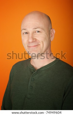 Confident middle-aged Caucasian man on orange background - stock photo