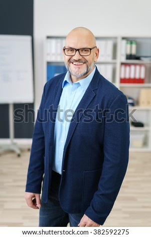 Confident middle aged handsome businessman with beard and bald head standing in business casual outfit with big smile - stock photo
