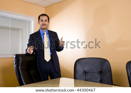 Confident middle-aged Hispanic businessman standing in boardroom - stock photo