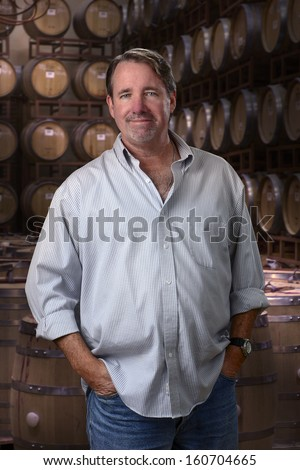 Confident middle aged man smiling in a room with wine barrels - stock photo