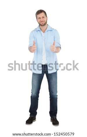 Confident model giving thumbs up to camera on white background - stock photo