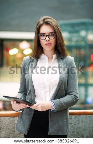Confident modern and young business woman holding tablet computer - stock photo