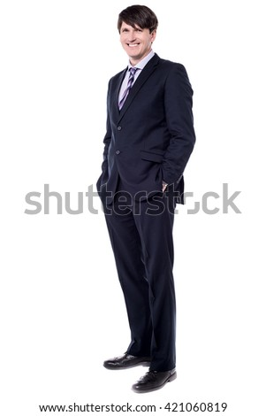 Confident modern businessman keeping his hands in trousers pockets