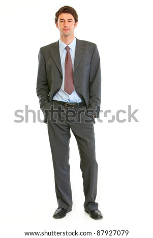 Confident modern businessman with hands in pockets isolated on white