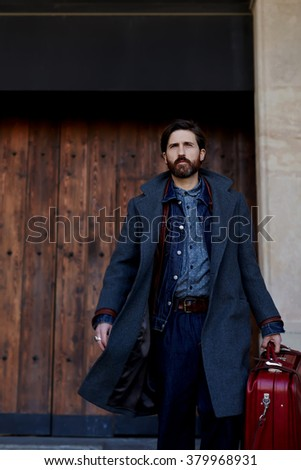 Confident modern tourist dressed in fashionable autumn clothes holding travel bag while going to his car, stylish bearded man with vintage red suitcase walking to hotel during fall business vacation - stock photo