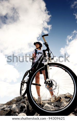 confident mountainbike rider standing and observing the view - stock photo