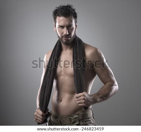 Confident muscular man drying his athletic body with a towel - stock photo
