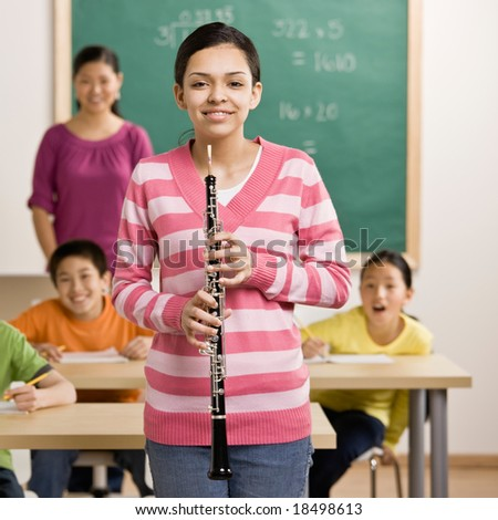Confident musician holds clarinet in school classroom