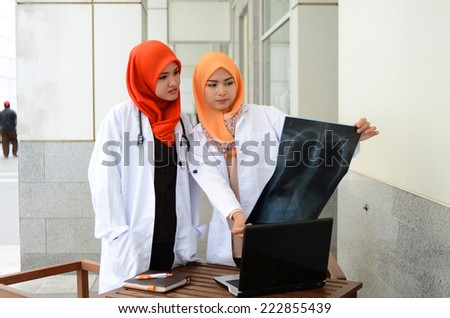 Confident Muslim medical student busy with doctor looking at patient's x-ray
