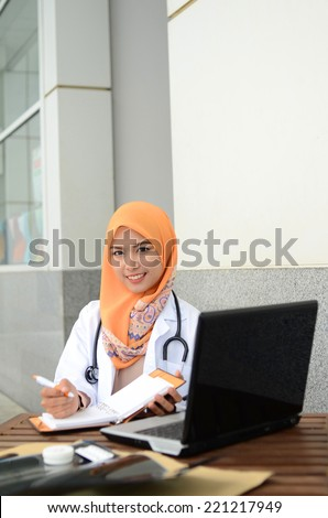 Confident Muslim medical student smile while study at hospital - stock photo