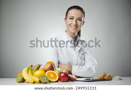 Confident nutritionist working at desk with fresh fruit - stock photo