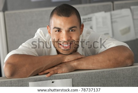 Confident office worker rests his chin on his arms - stock photo