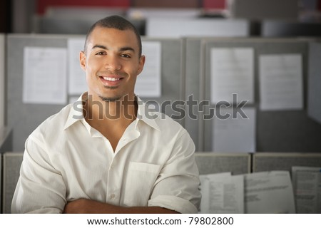 Confident office worker smiles in his office cubicle - stock photo