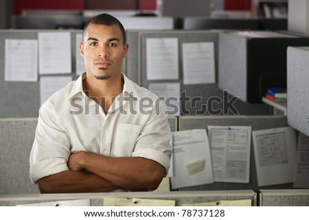 Confident office worker with hands folded standing in his cubicle - stock photo