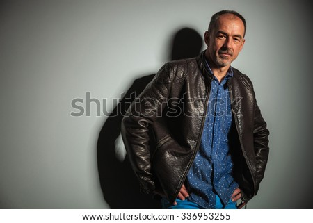 confident old casual man in leather jacket and jeans standing with hands on hips in studio