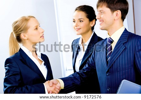 Confident partners shaking hands making an agreement at meeting - stock photo