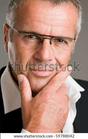 Confident pensive mature man with glasses looking at camera satisfied