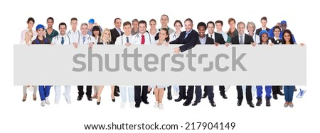 Confident people with various occupations holding blank banner over white background - stock photo