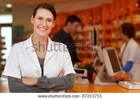 Confident pharmacist with her arms crossed in a pharmacy - stock photo
