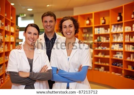 Confident pharmacy team with pharmacist and pharmacy technicians - stock photo