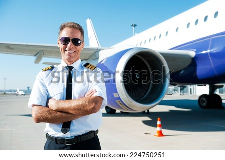 Confident pilot. Confident male pilot in uniform keeping arms crossed and smiling with airplane in the background  - stock photo
