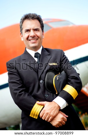 Confident pilot smiling with an airplane at the background - stock photo