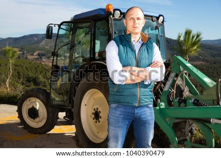 Confident pleasant  male owner of vineyard posing near tractor outdoors in sunny day