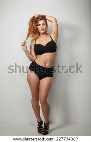Confident plus size young woman in black bikini posing on grey background. Full length image of healthy young woman posing sensually. - stock photo