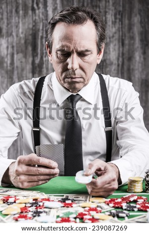 Confident poker player. Serious senior man in shirt and suspenders sitting at the poker table and holding cards and chips  - stock photo