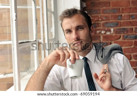 confident portrait of an attractive man next to window