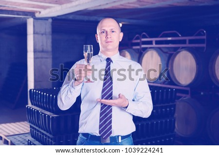 Confident positive cheerful  winemaker offering glass of white sparkling wine for tasting in wine cellar