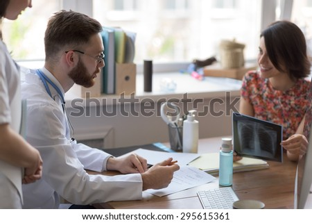 Confident practitioner consulting woman in hospital. Explaining results of chest x-ray scan - stock photo