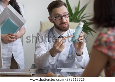 Confident practitioner consulting woman in hospital. Prescribing treatment - stock photo